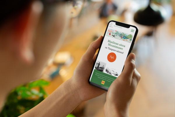 Henkilö katselee muumimuseo.fi etusivua iPhonella.