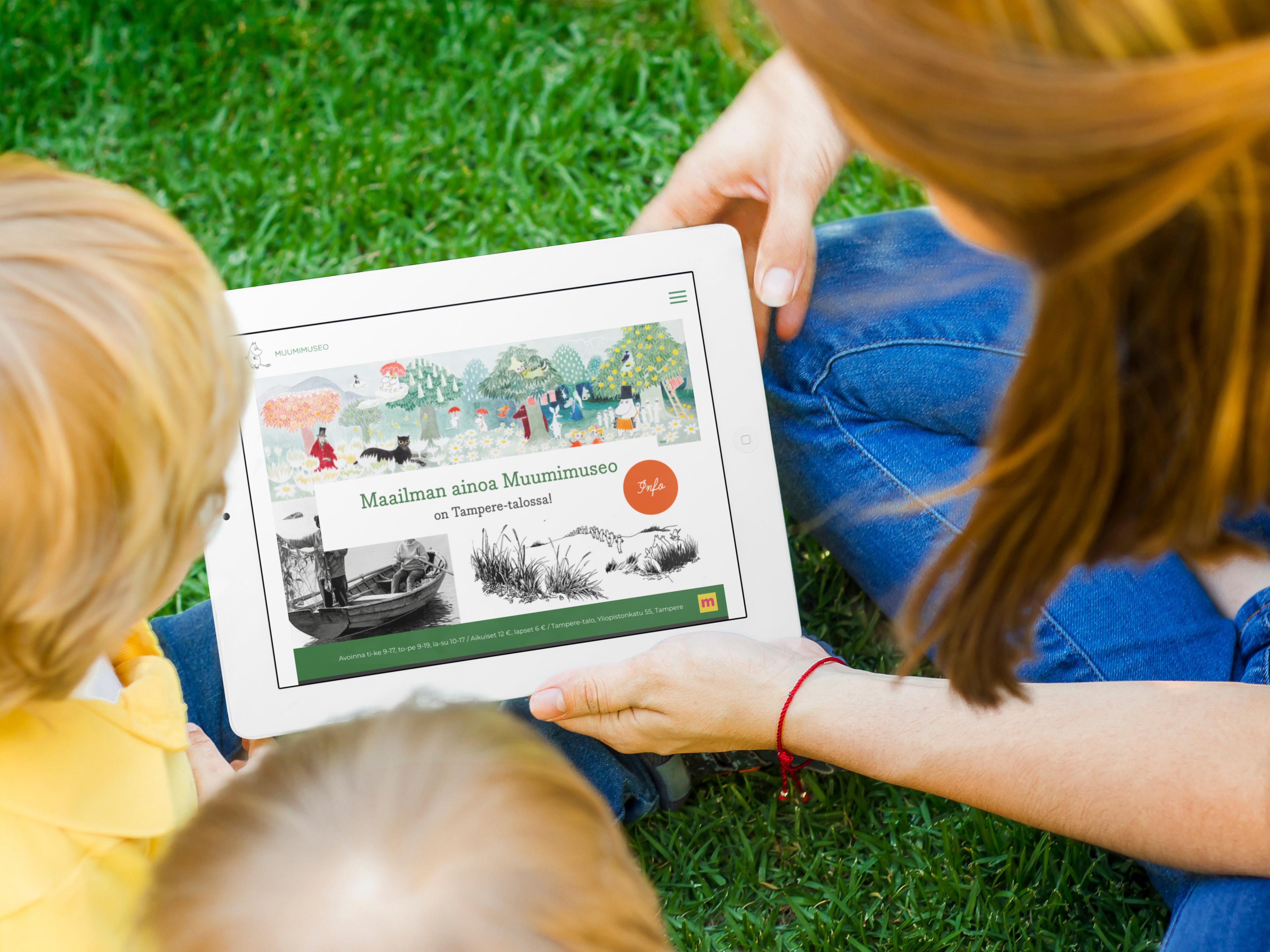 Kolme ihmista katselee muumimuseo.fi etusivua iPadilla.