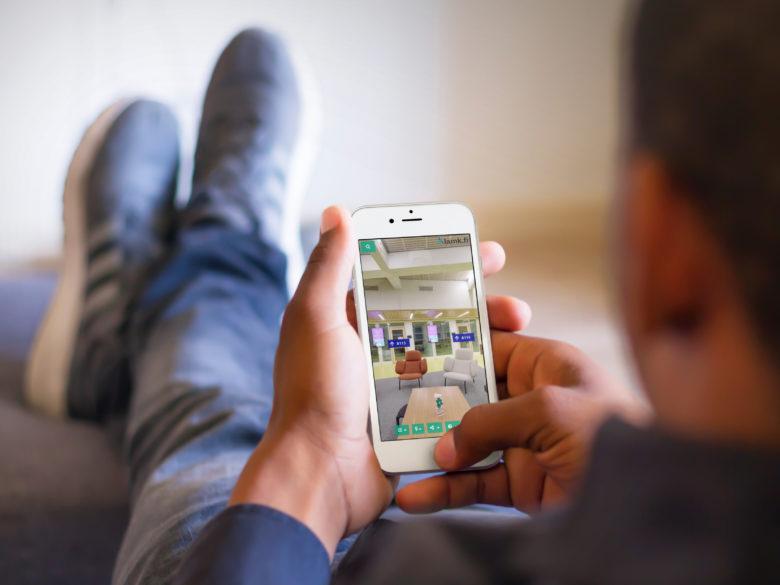 Mies istuu sohvalla ja katselee LAMK 360 palvelua älypuhelimella.