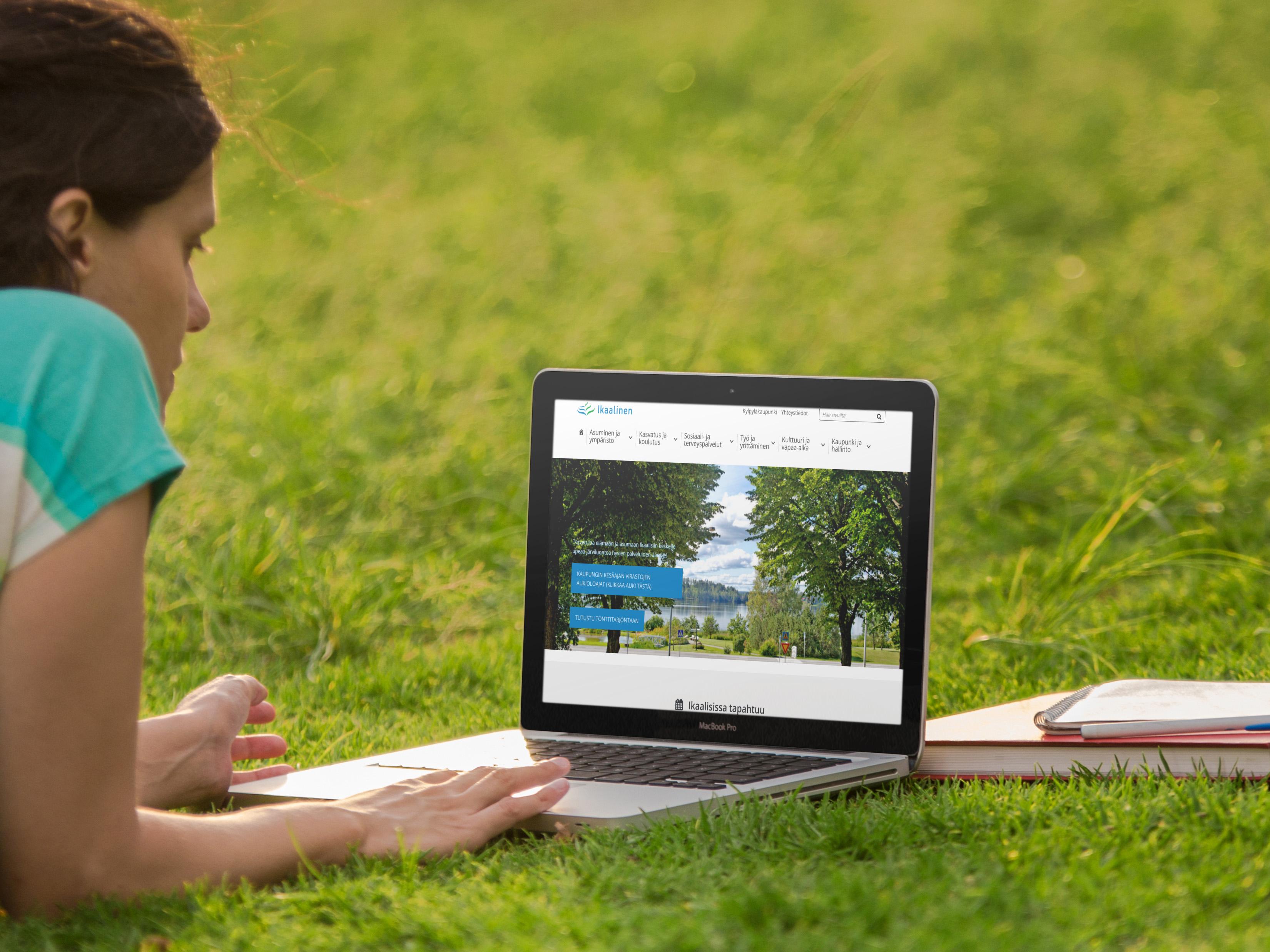 Nainen katselee ikaalinen.fi etusivua kannettavan tietokoneen näytöltä nurmikolla.