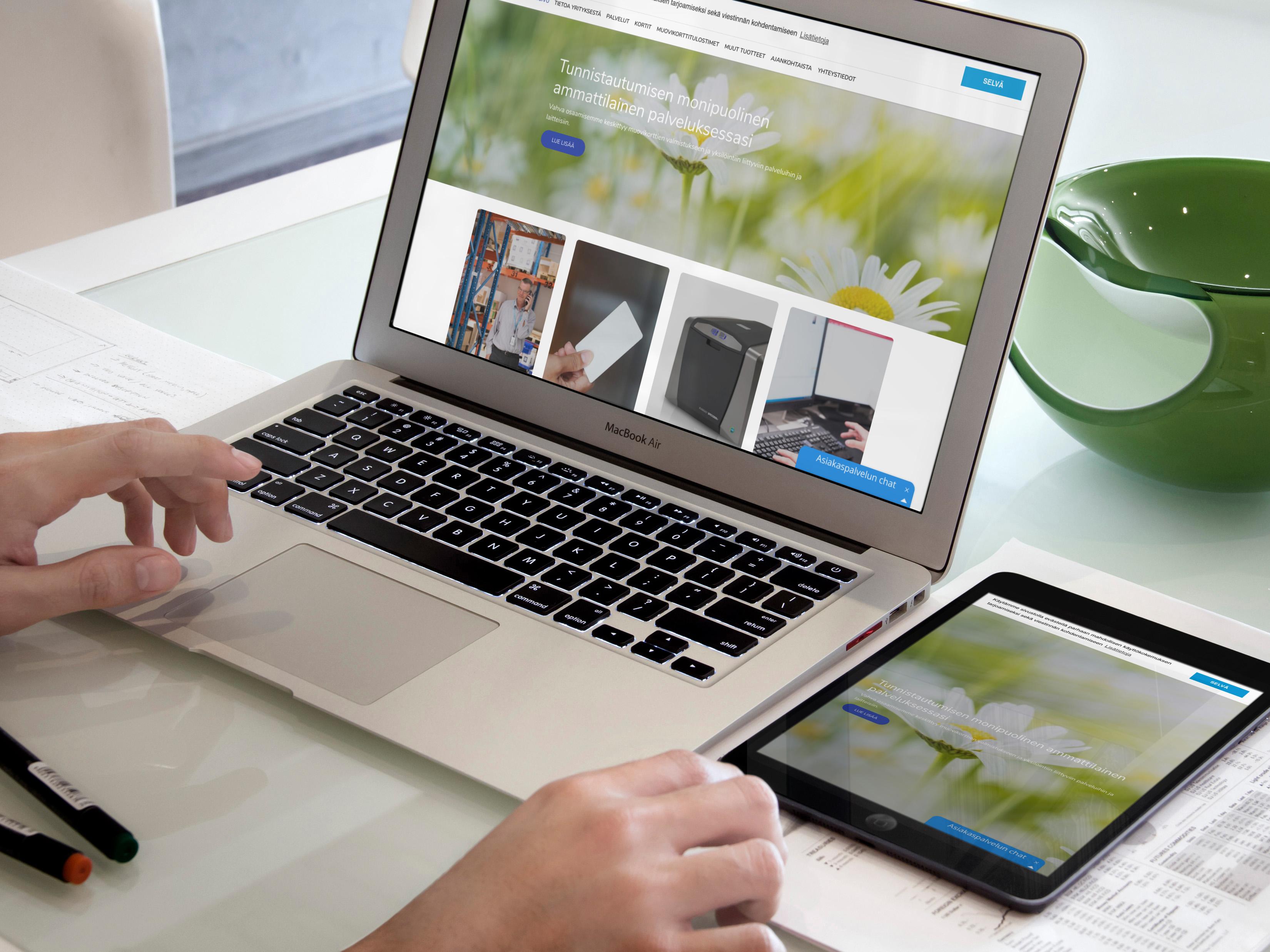 Henkilö katselee cardplus.fi sivustoa kannettavalla tietokoneella ja tabletilla.