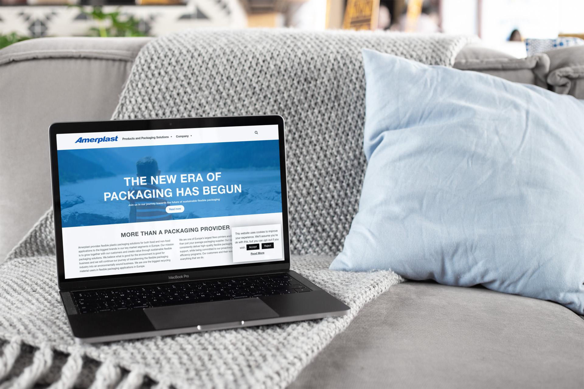 Läppäri sohvalla, jonka näytöllä amperlast.com etusivu.
