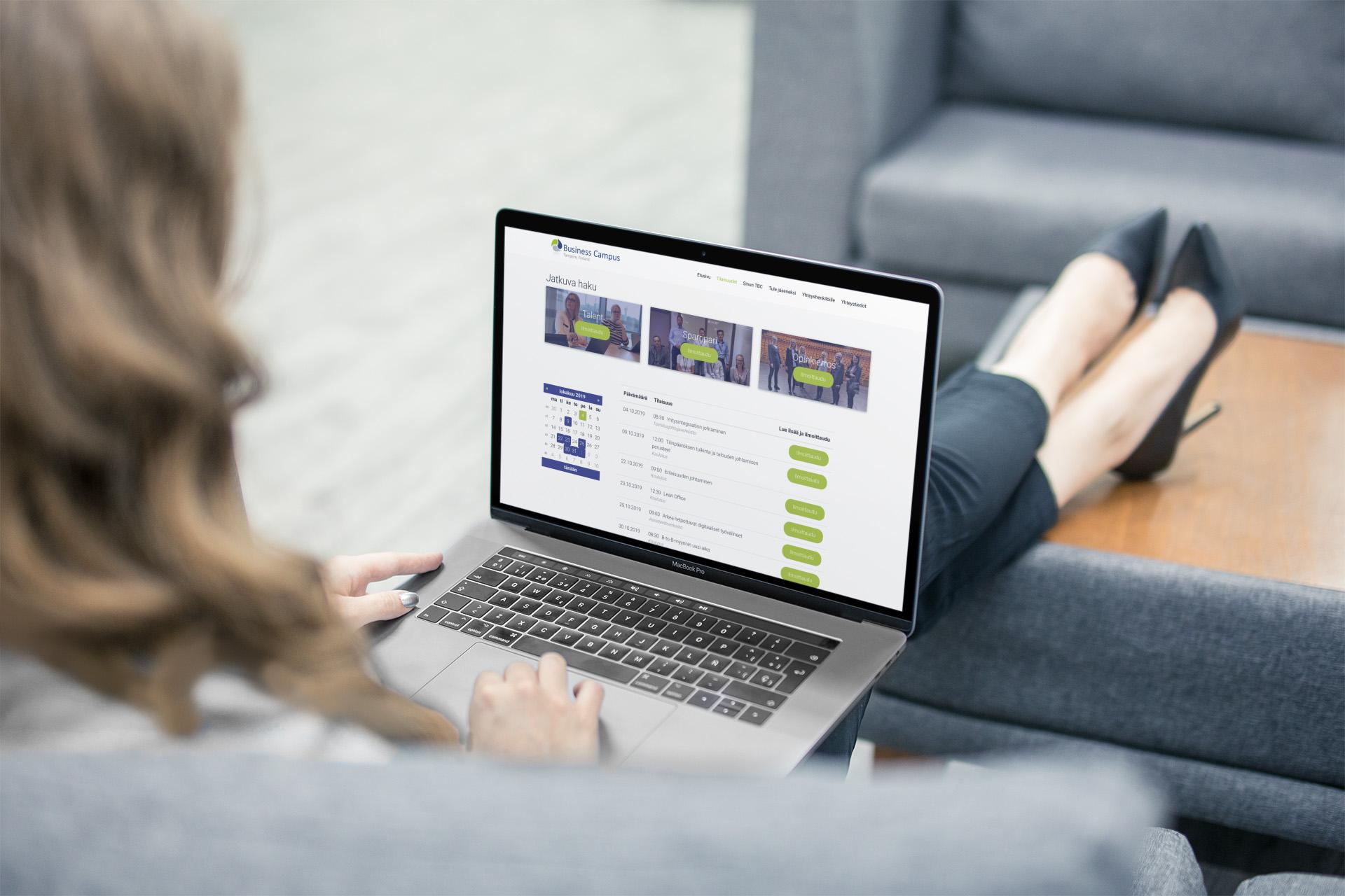 Nainen istuu sohvalla ja katselee businesscampus.fi tilaisuudet sivua läppärillä.