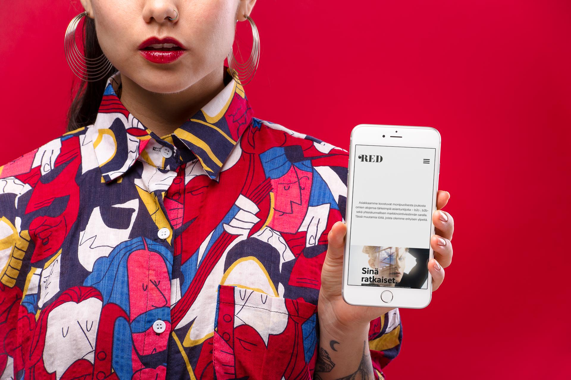 Nainen esittelee työmme sivun mobiilinäkymää iPhone kädessään.