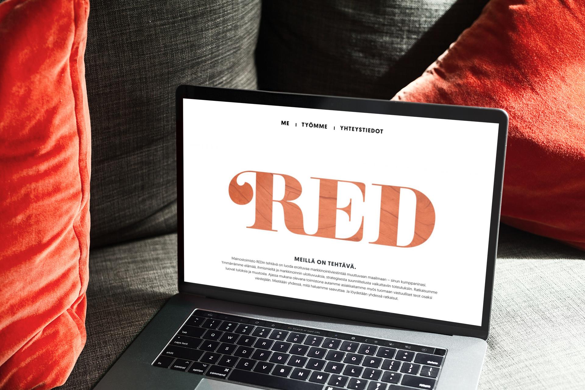 Mainostoimisto RED etusivu sohvalla olevan läppärin näytöllä.