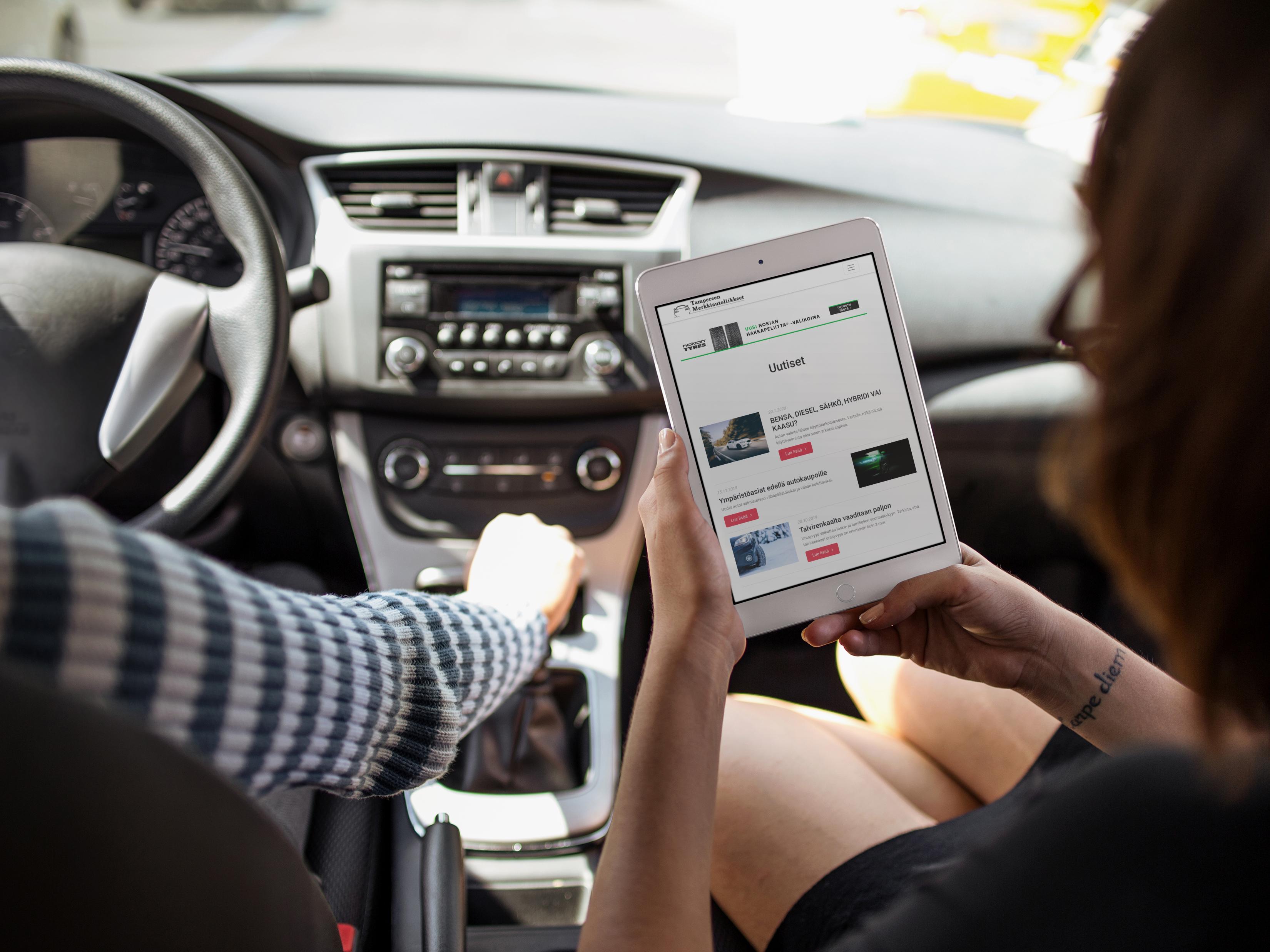 Nainen lukee Tampereen Merkkiautoliikkeiden uutisia autossa tabletilla.
